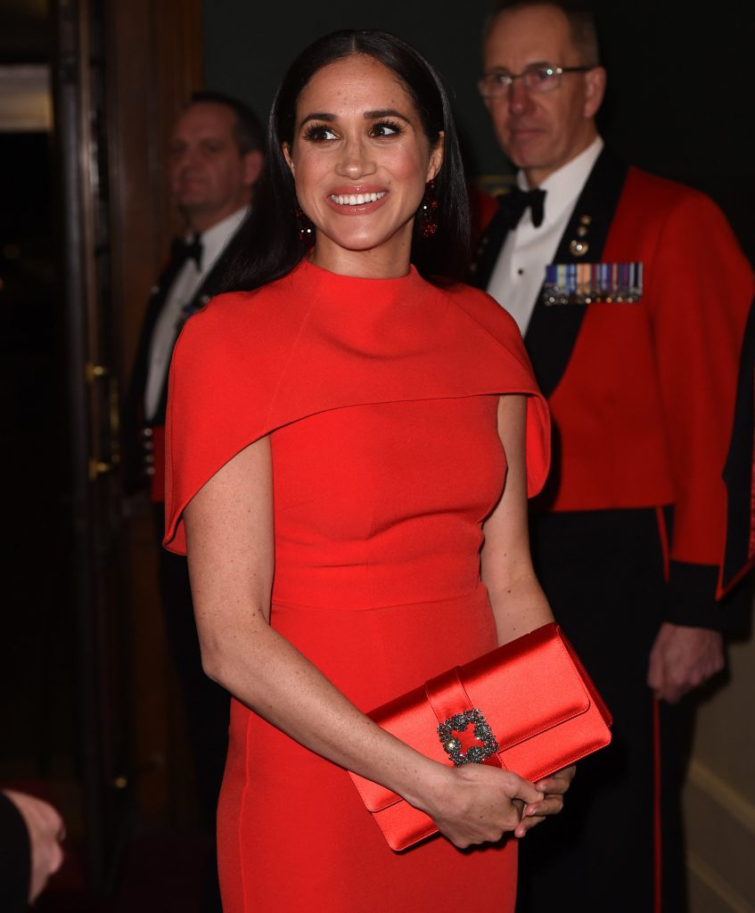 Meghan Markle smiling in a red dress