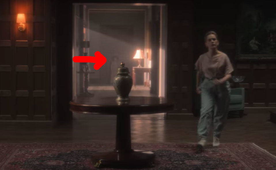 Dani moves through the foyer of Bly Manor; a red arrow points to a ghost child in the background behind her