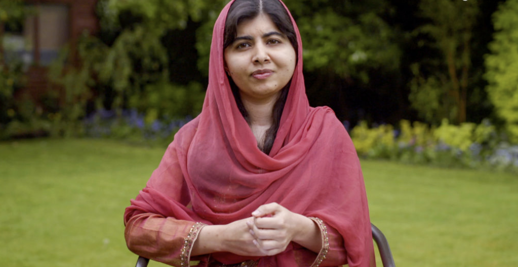 Malala sitting outside in a chair on the grass