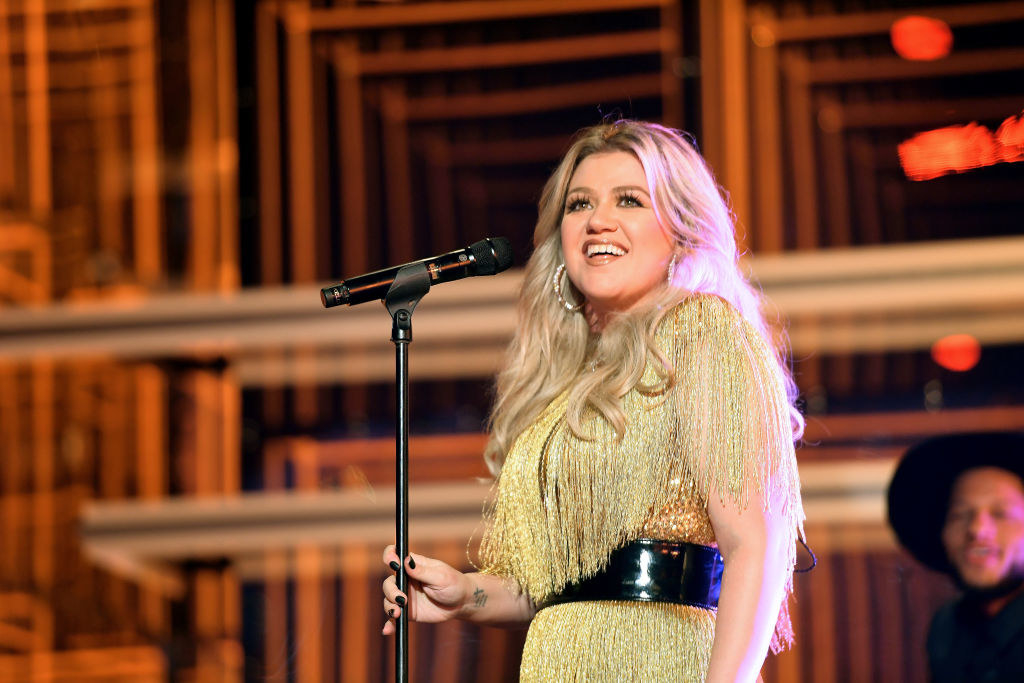 Kelly smiling onstage next to a microphone