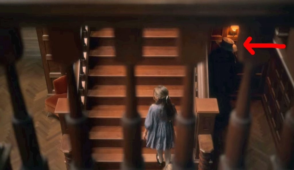 Flora walks up the stairs; a red arrow points to a figure in a hat lurking in the corner below the stairs
