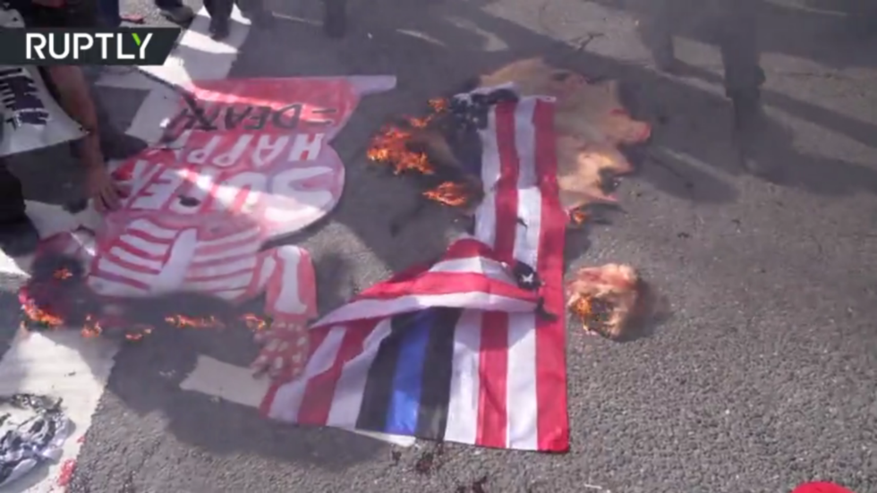 Man 'eats a heart' over burning US flag as anti-Trump protesters face off with the president's supporters in Boston (VIDEO)