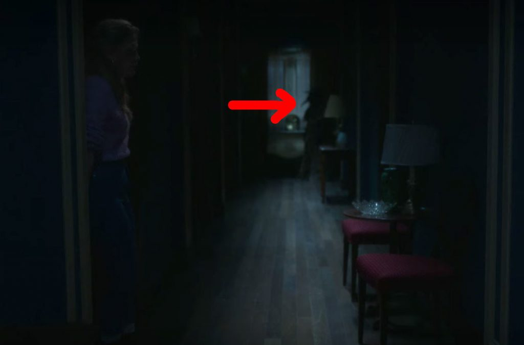 Dani exits Flora's room; at the end of the hallway a red arrow points to the silhouette of the plague doctor