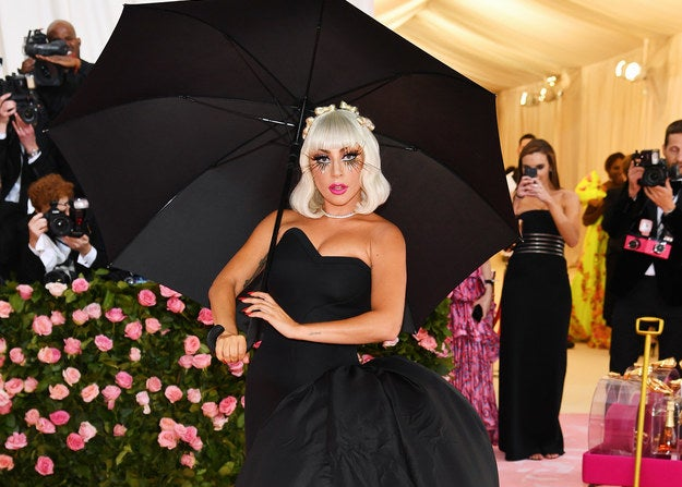 Lady Gaga posing with large black umbrella