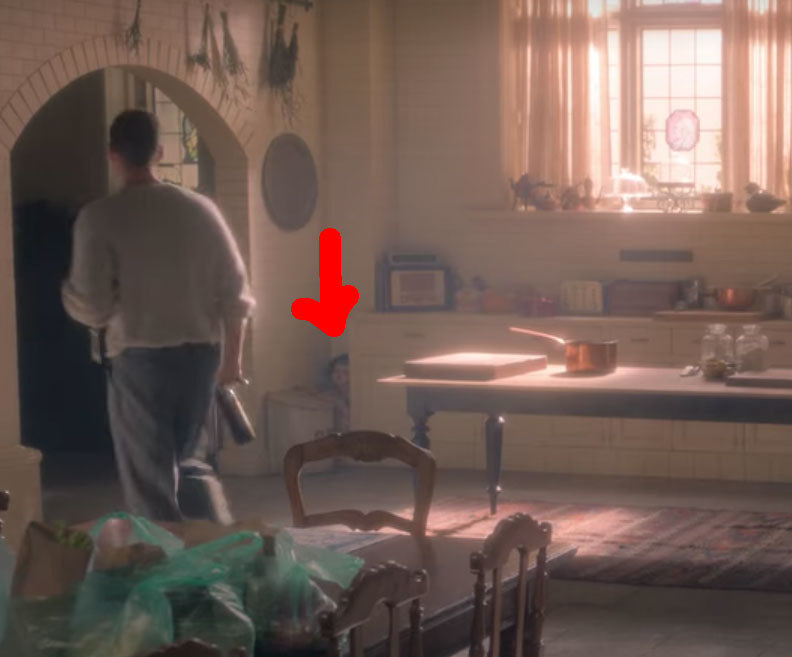 Peter walks out of the kitchen; near him a red arrow points to a doll-faced figure crouched in the corner
