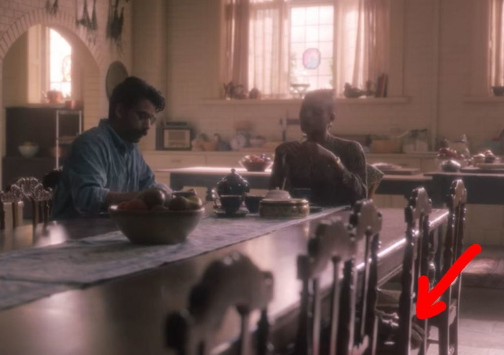 Hannah and Owen sit at the kitchen table; a red arrow points to a child's pair of hands resting on an empty chair at the table
