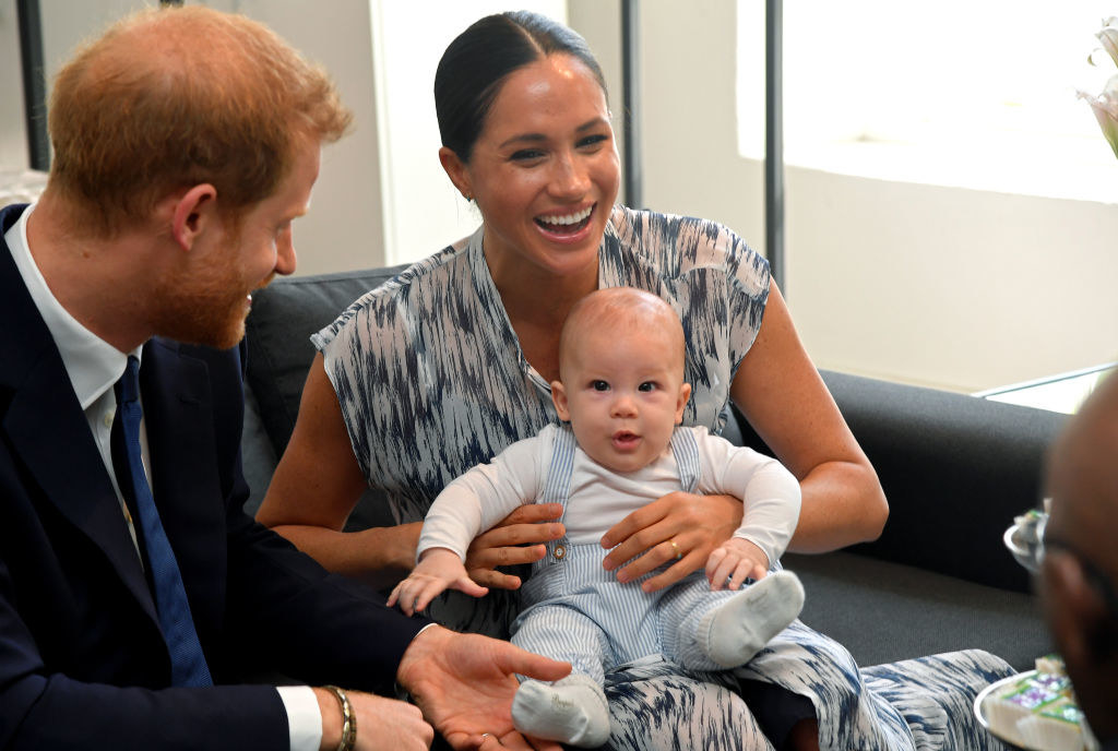 Meghan laughing with Archie on her lap