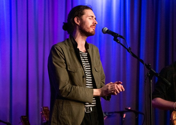 Hozier at a microphone singing on stage