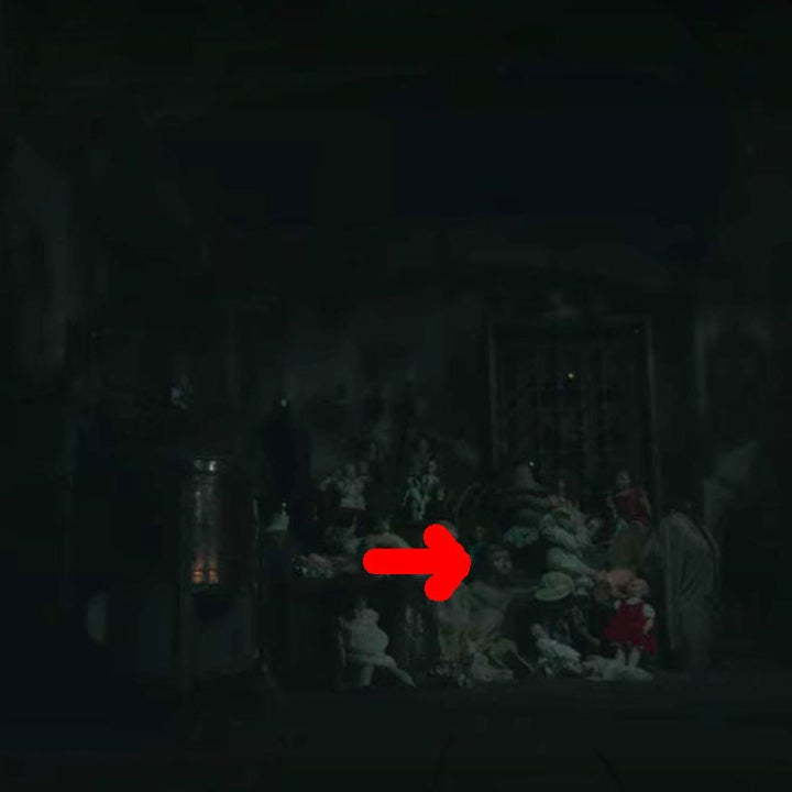 A red arrow pointing to the boy ghost with the doll face, sitting up amongst dolls in the darkened basement
