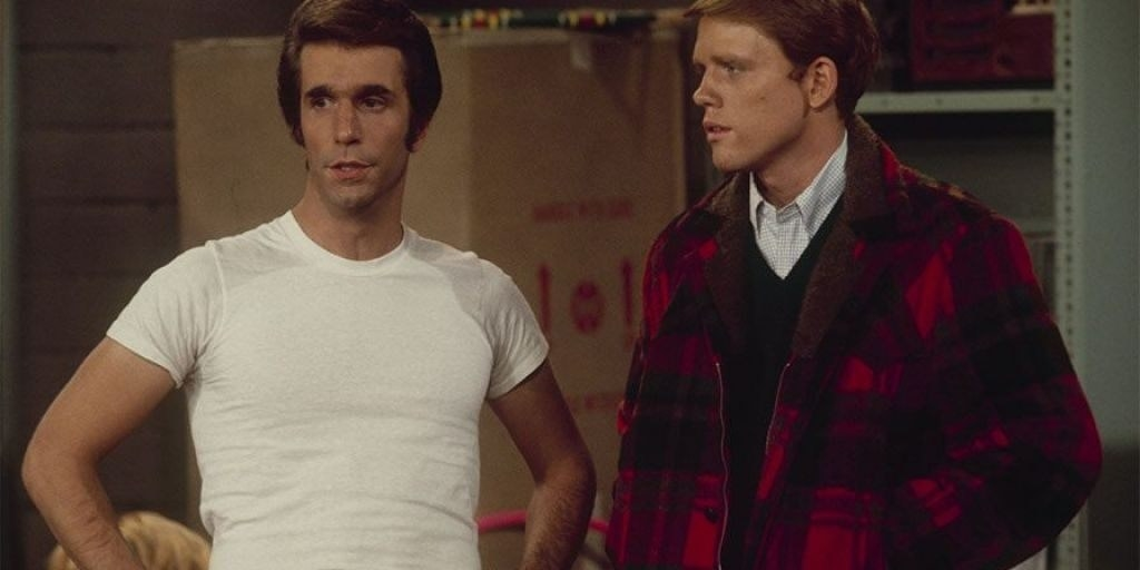 Fonzie puffing his chest next to another white man.