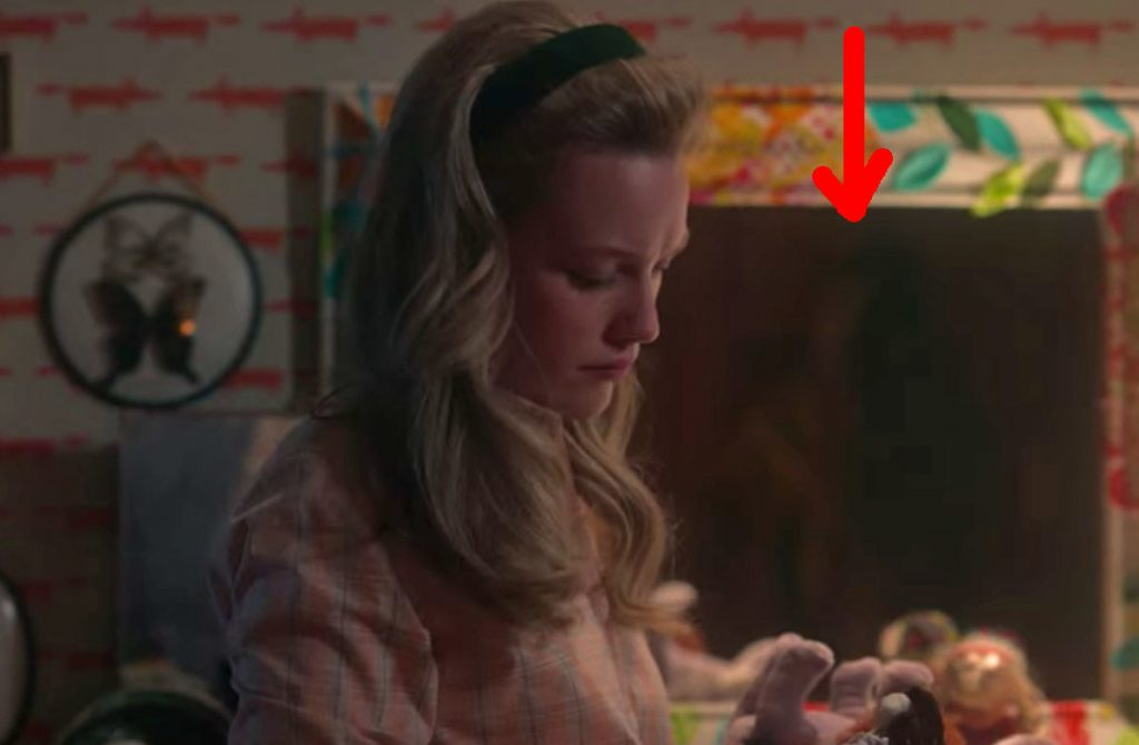 Dani stands in front of a mirror in Flora's room looking at a doll; a red arrow points to an indistinct figure seen in the reflection