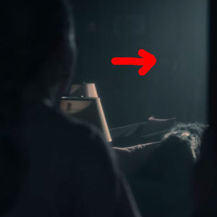 Dani looks into the dark classroom; a red arrow points out a shadowy figure