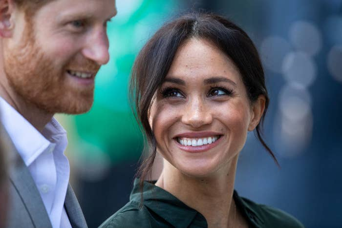 Meghan smiling big and looking up at Harry