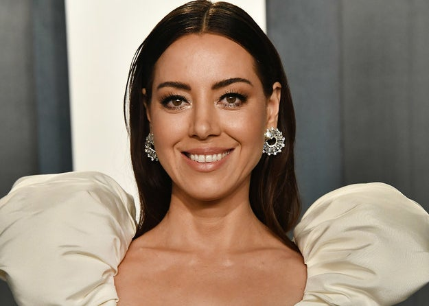 Aubrey Plaza smiling in formal gown with puffy shoulders