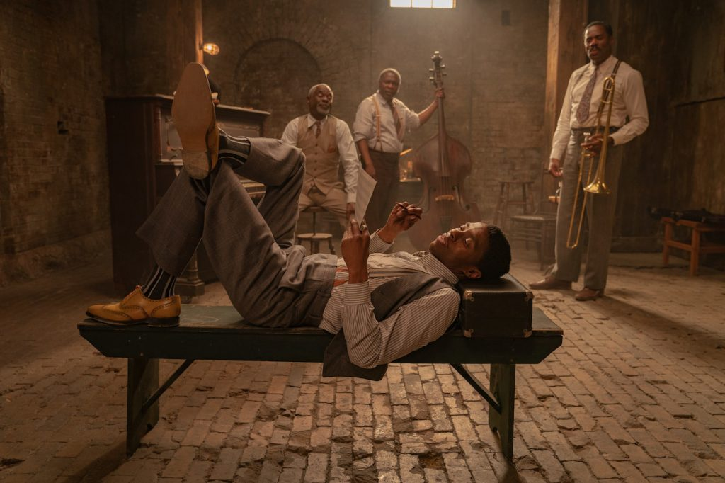 Chadwick laying on a bench in a basement while men with instruments stand in the background