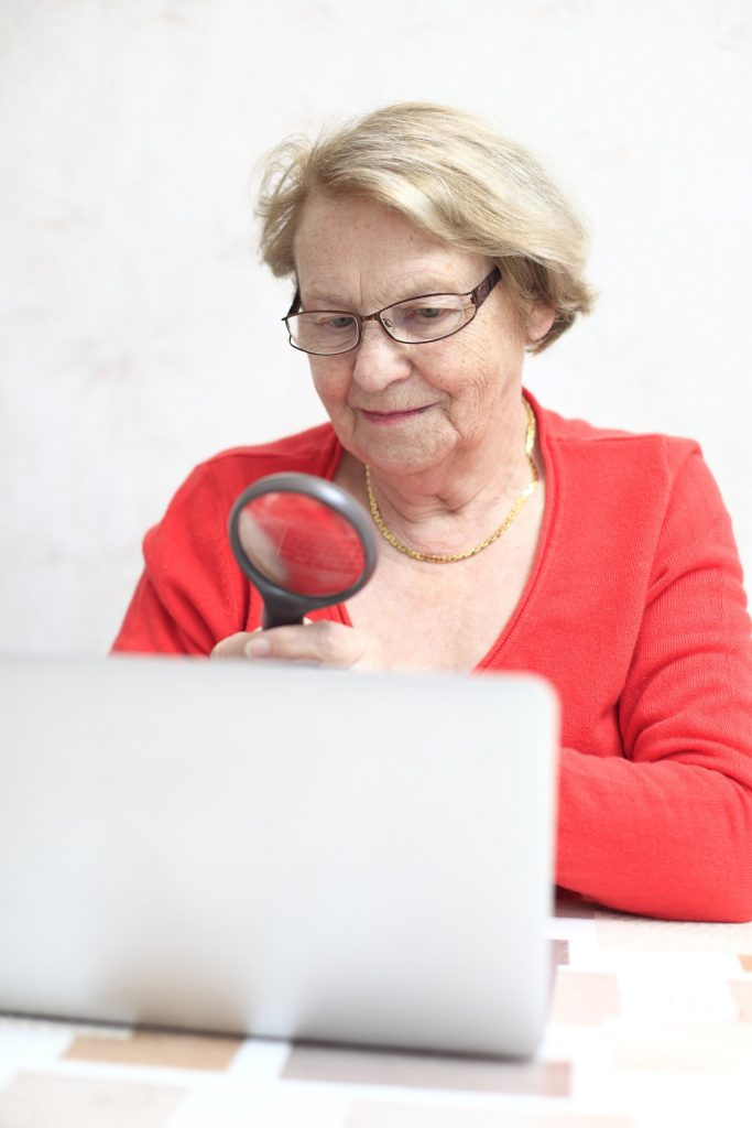 elderly woman with a magnifying glass looking at a laptop