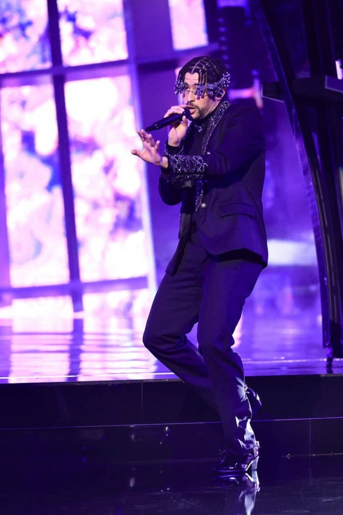 Bad Bunny in an all-black suit performs on stage.