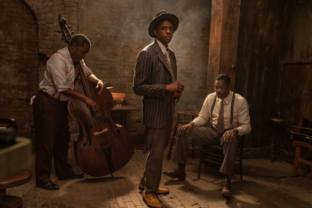 Chadwick Boseman wearing a suit and staring at the camera while men tune instruments behind him