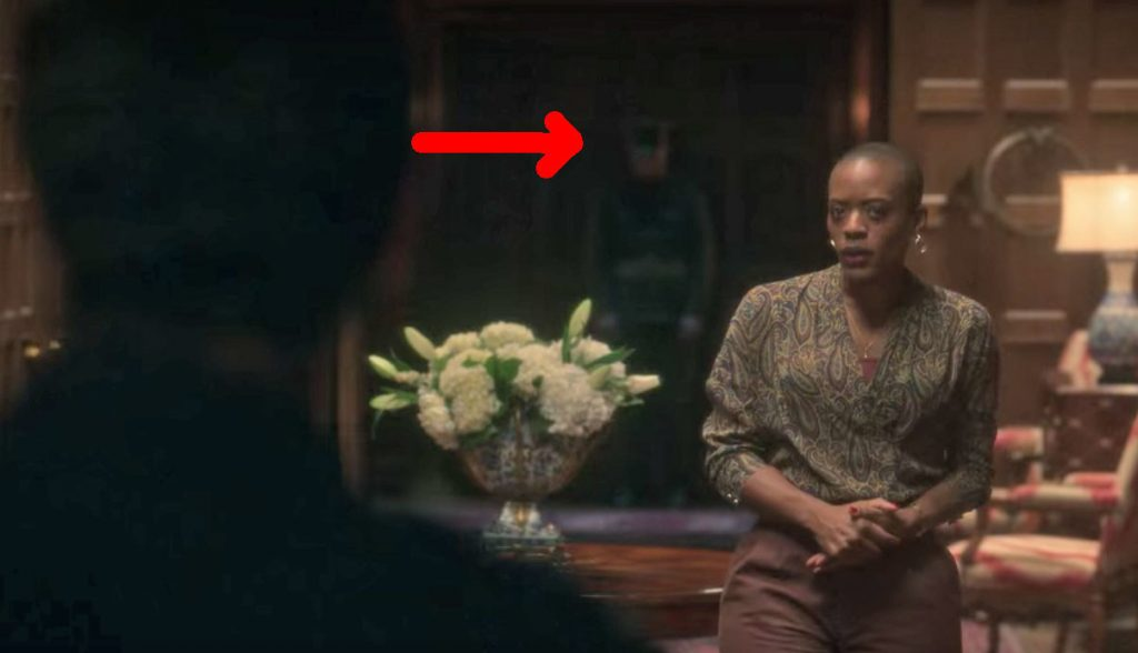 Hannah stands in the foyer talking to the police officer; behind her in the background a red arrow points to the ghost of a soldier