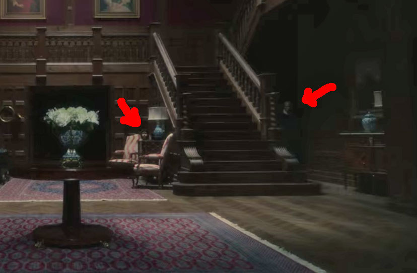 The foyer of Bly Manor with red arrows pointing to the ghost boy and a pale man on either side of the staircase