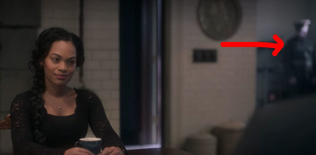 Rebecca sits at the kitchen table with a cup of tea; to the far right a red arrow points to the out of focus soldier ghost