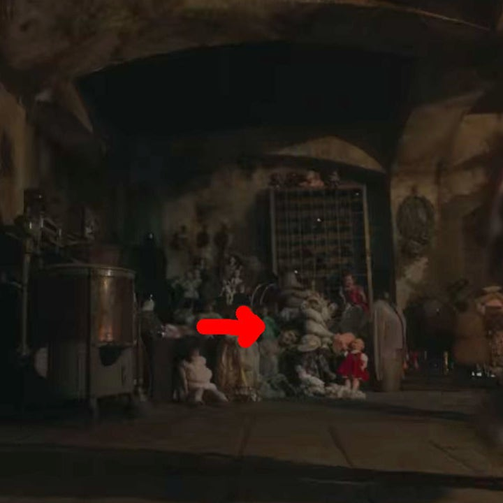 A red arrow pointing to a little boy ghost with a doll face leaning on an actual doll in the basement