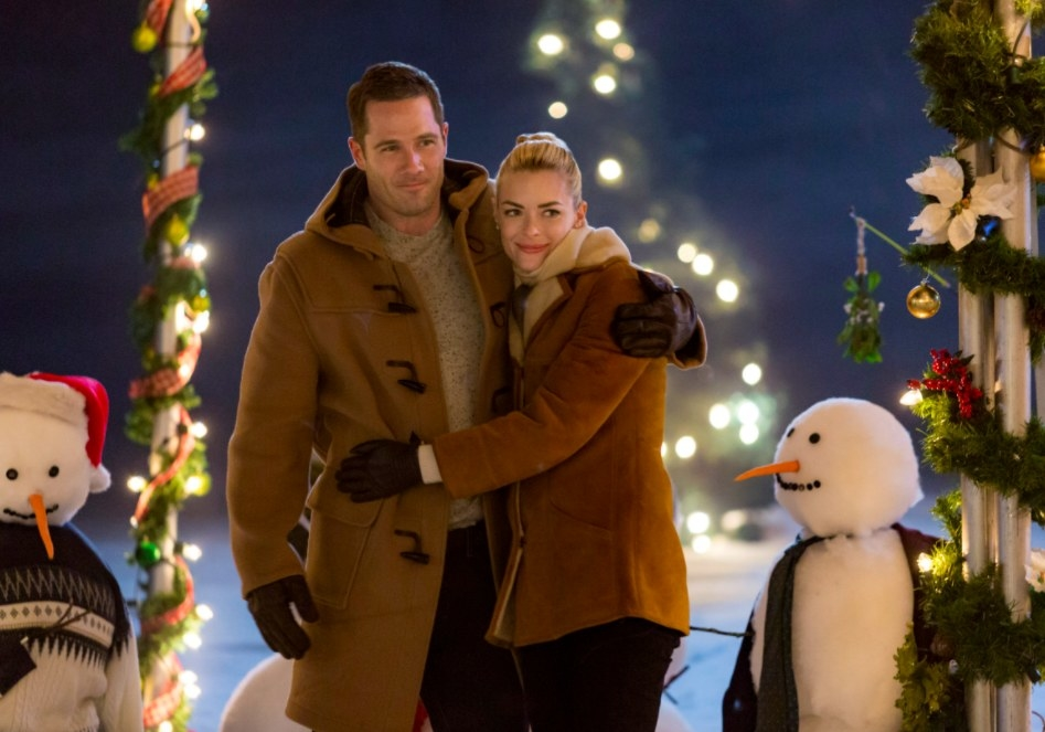 Still from The Mistletoe Promise: Jaime King and Luke McFarlane embrace surrounded by snowmen and Christmas decorations