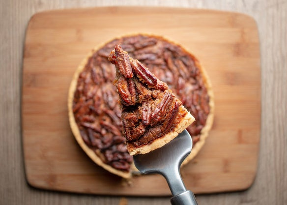 A slice of pecan pie held up above the rest of the pie