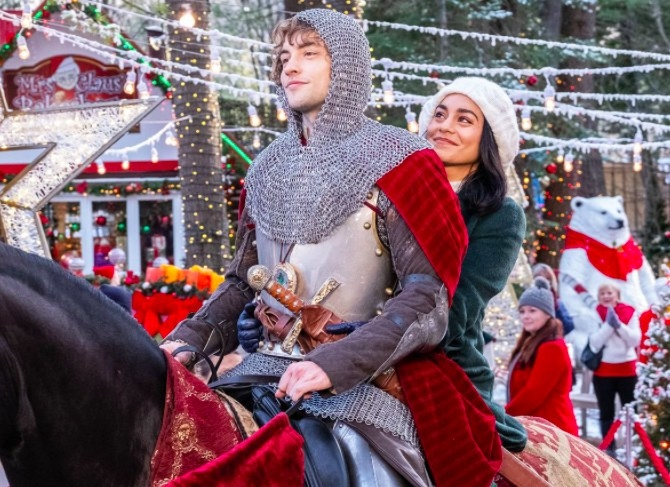 Still from The Knight Before Christmas: Vanessa Hudgens and Josh Whitehouse ride a horse together; he is wearing a knight costume