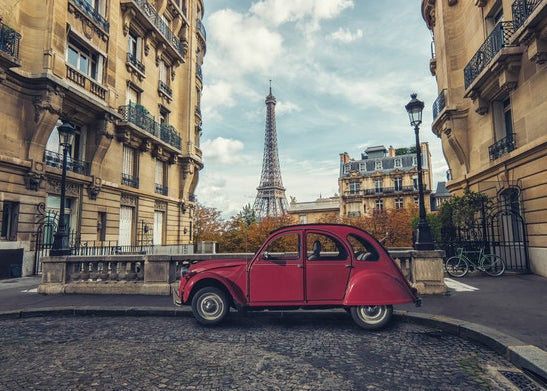 An old car parked in an alcove between buildings overlooking the Eiffel Tower
