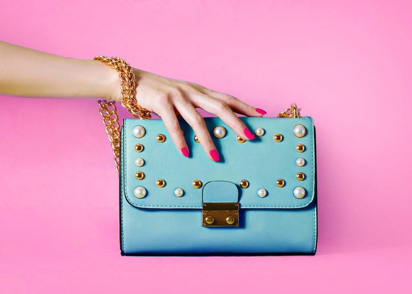 A hand holding a large clutch purse with decals