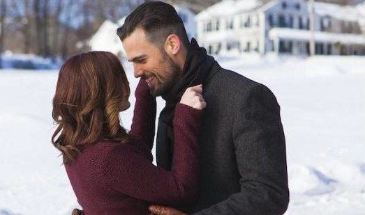 Still from The Spirit of Christmas: Jen Lilley and Thomas Beaudoin embrace in front of a snow-covered lawn