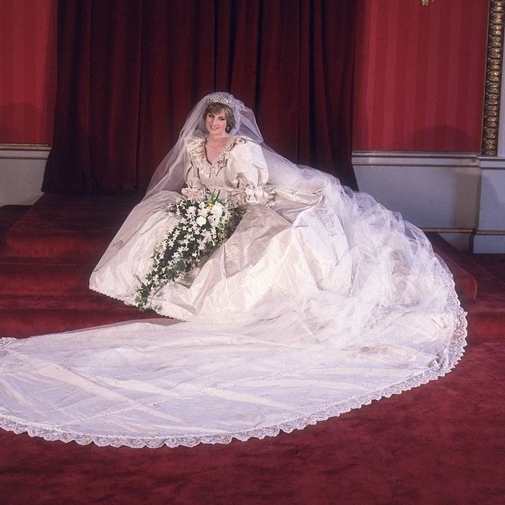 Princess Diana sitting on the floor as she poses for a photo in her wedding gown