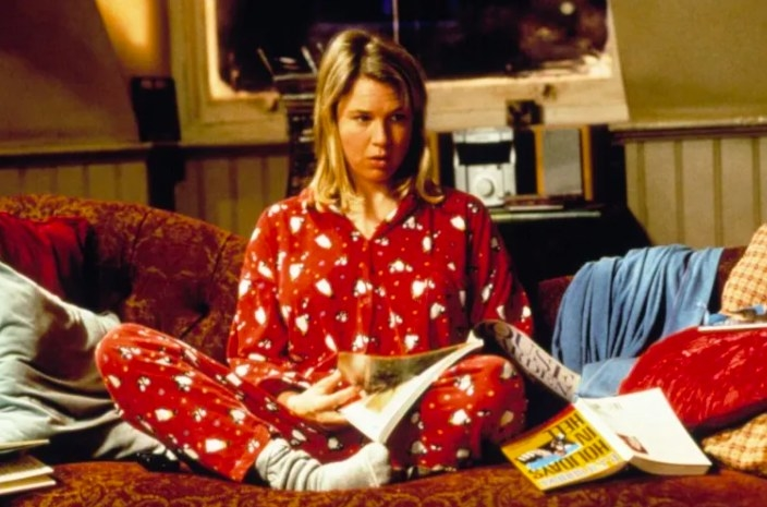 Still from Bridget Jones's Diary: Renee Zellweger sits on a couch in pyjamas and socks reading a magazine