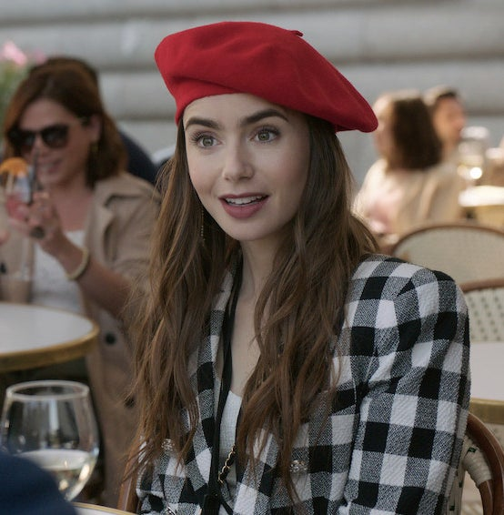A still of Emily sitting a cafe table and wearing a beret