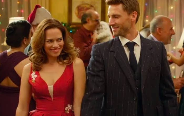 Still from Snowed Inn Christmas: Bethany Joy Lenz and Andrew Walker hold hands at a party while wearing formal clothes