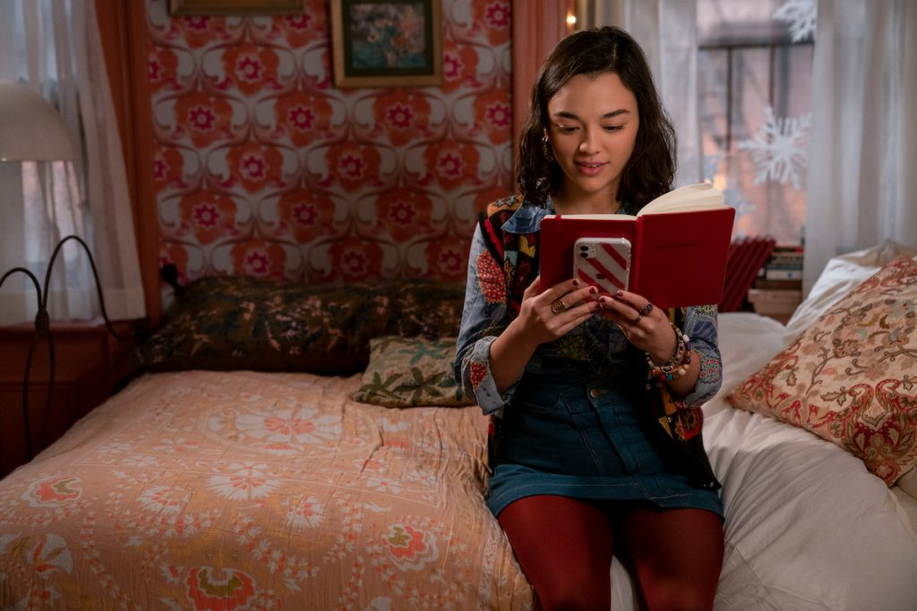 Lily sitting on a bed reading the notebook