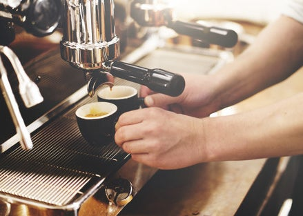Hands making small cups of coffee