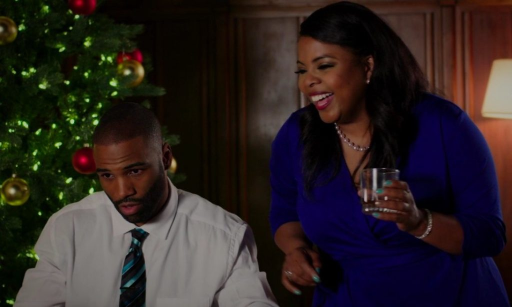 Still from You Can't Fight Christmas: Brely Evans stands next to Andra Fuller with a drink in hand