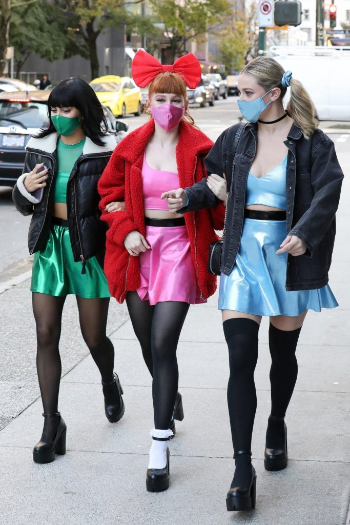 powerpuff girl costumes with heels, tights, shiny skater skirts, crop tops, jackets, and matching colored masks