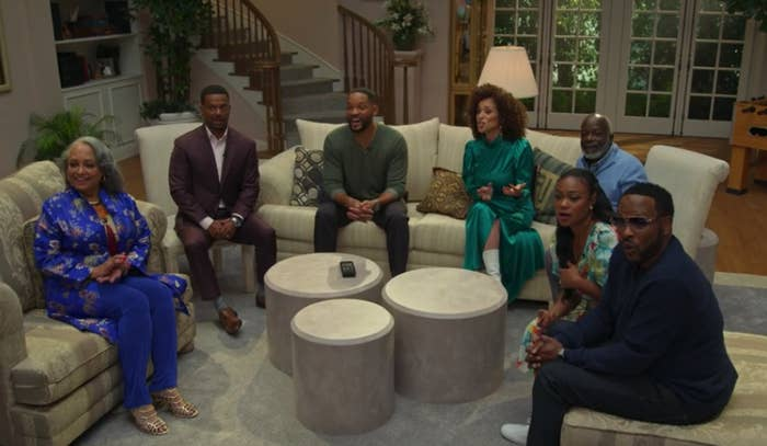 "Daphne Maxwell Reid, Alfonso Ribeiro, Will Smith, Karyn Parsons, Joseph Marcell, Tatyana Ali, and DJ Jazzy Jeff sitting in a replicated living room from ""The Fresh Prince"""