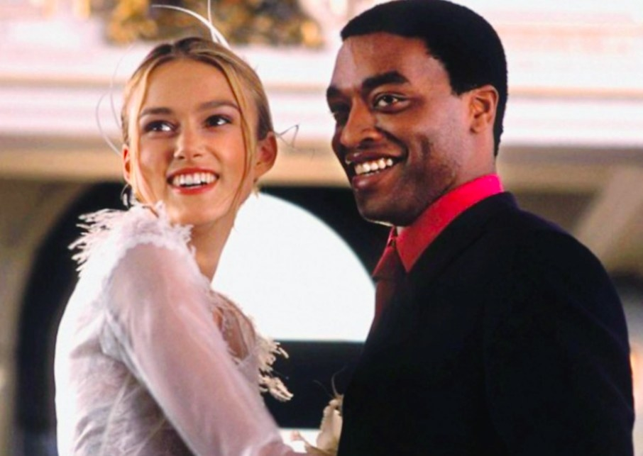Still from Love Actually: Keira Knightley and Chiwetel Ejiofor wear wedding clothes and stand close together, smiling
