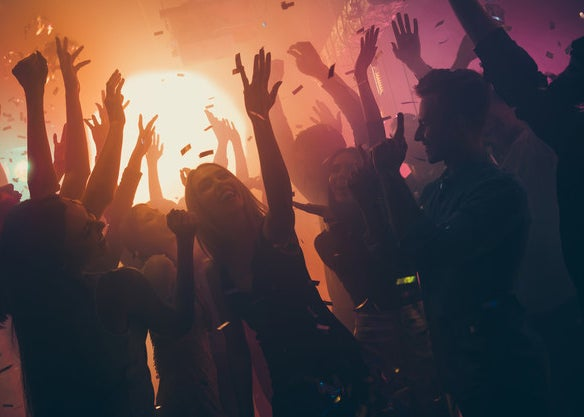 People dancing at a party with confetti in the air