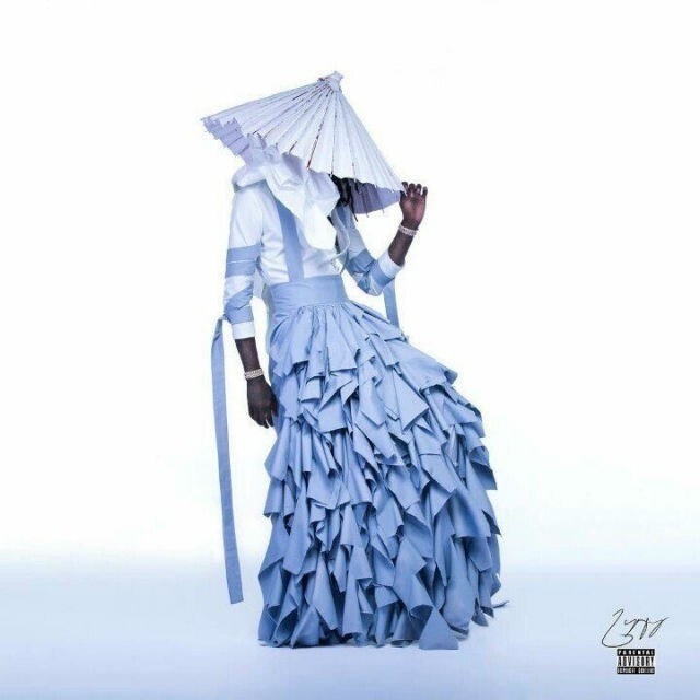 Young Thug in a dress with 3/4 sleeves and a large ruffled skirt with a belt that also wraps up over the shoulders and around the arms, and a pointed long hat