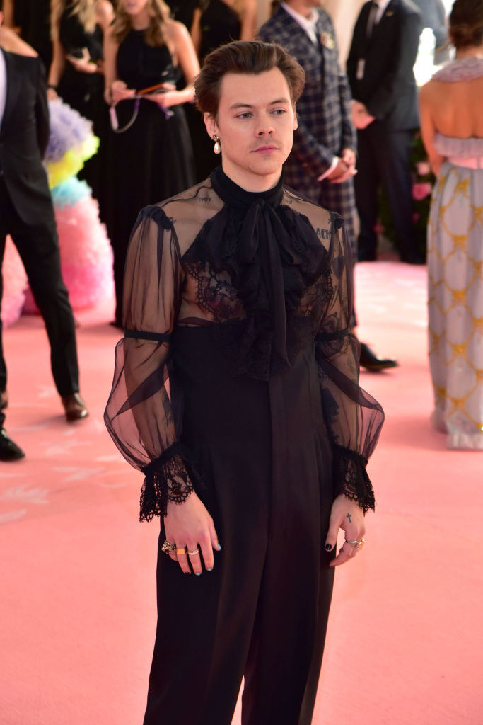 Harry in a sheer lacy top jumpsuit with bell sleeves and a ruffle at the top then loose bants