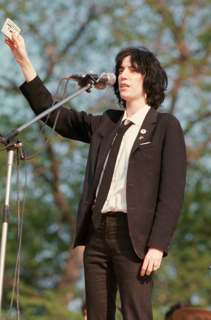 Patti in tight dark jeans and a suit jacket with a button up and tie underneath