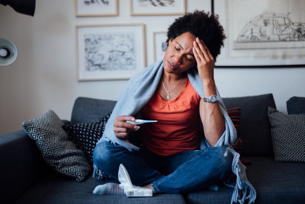 Worried Black woman sitting on coach while being sick