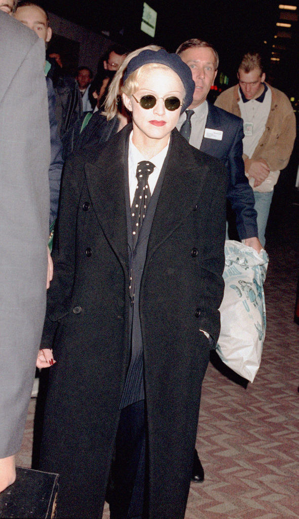 Madonna in a suit jacket with a tie underneath, dark loose pants, and a long peacoat on top