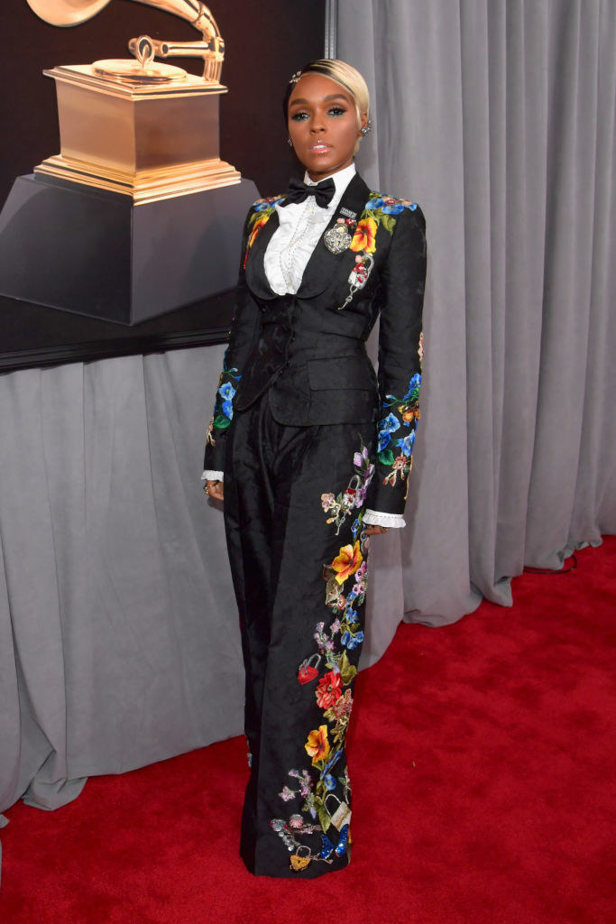 Janelle in a floral patterned tuxedo suit with loose pants and a frilled button up with bowtie