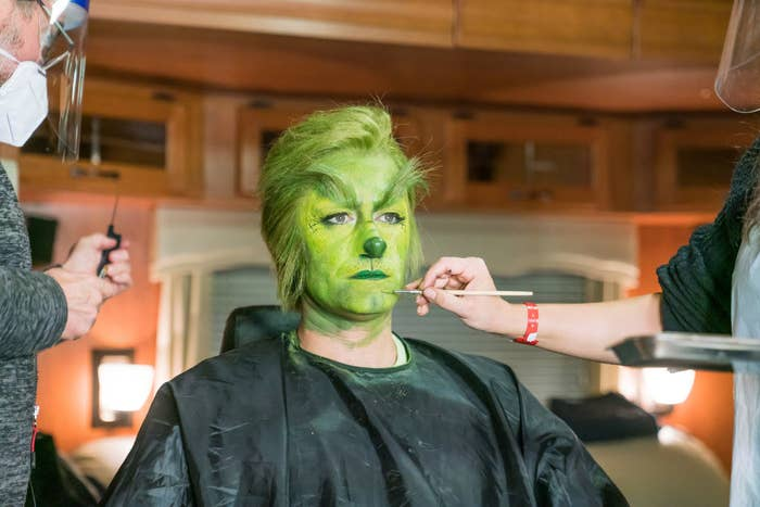 Matthew Morrison sitting in the makeup chair getting his grinch makeup applied.